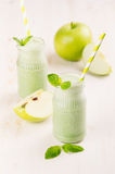 Freshly blended green apple fruit smoothie in glass jars with straw, mint leafs, apples. White wooden board background, copy space Royalty Free Stock Photo