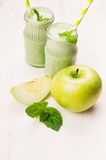 Freshly blended green apple fruit smoothie in glass jars with straw, mint leafs, apples. White wooden board background, copy space. Freshly blended green apple Stock Photos