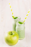 Freshly blended green apple fruit smoothie in glass jars with straw, mint leafs, apples. White wooden board background, copy space Stock Images