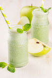 Freshly blended green apple fruit smoothie in glass jars with straw, mint leafs, apples. White wooden board background, copy space Stock Photography