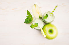 Freshly blended green apple fruit smoothie in glass jars with straw, mint leafs, cut apples, top view. White wooden board backgrou Royalty Free Stock Photos