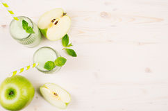 Freshly blended green apple fruit smoothie in glass jars with straw, mint leafs, cut apples, top view. Stock Image