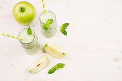 Freshly blended green apple fruit smoothie in glass jars with straw, mint leafs, cut apples, top view. Stock Photo