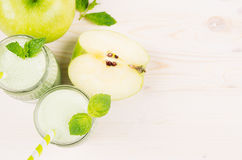 Freshly blended green apple fruit smoothie in glass jars with straw, mint leafs, cut apples, top view. Stock Photos