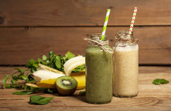 Freshly blended green and banana smoothies in glass bottles with straws. Freshly blended green and banana smoothies in glass bottles with straws on wooden Royalty Free Stock Images