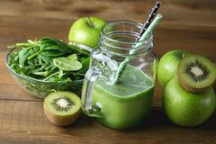 Freshly Blended Green Fruit Smoothie in Glass Jar with Straw. Spinach Aragula Green Apple Kiwi Detox Healthy Food Toned. / stock photo