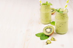 Freshly blended green kiwi fruit smoothie in glass jars with straw, mint leaf, cute ripe berry, copy space. White wooden board background Stock Image