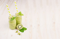 Freshly blended green kiwi fruit smoothie in glass jars with straw, mint leaf, cute ripe berry, copy space. White wooden board background Stock Photography
