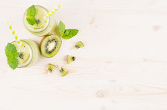 Freshly blended green kiwi fruit smoothie in glass jars with straw, mint leaf, cute ripe berry, top view. White wooden board backg. Round, decorative border Stock Image