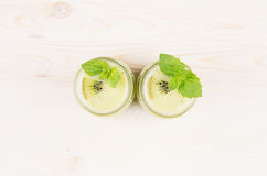 Freshly blended green kiwi fruit smoothie in glass jars with straw, mint leaf, top view. White wooden board background, copy space Royalty Free Stock Photography