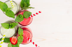 Freshly blended green and red fruit smoothie close up in glass jars with straw, mint leafs, top view. White wooden board backgroun. Freshly blended green and red Royalty Free Stock Images