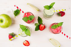 Freshly blended green and red fruit smoothie close up in glass jars with straw, mint leafs, top view. White wooden board backgroun Royalty Free Stock Photo
