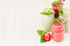 Freshly blended green and red fruit smoothie  in glass jars with straw, mint leafs of strawberry and apples. Stock Photos