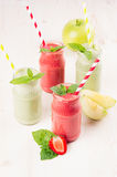 Freshly blended green and red fruit smoothie  in glass jars with straw, mint leafs of strawberry and apples. White wooden board ba Stock Photography