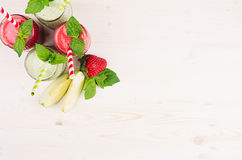 Freshly blended green and red fruit smoothie in glass jars with straw, mint leafs, top view. White wooden board background, copy space Royalty Free Stock Photography