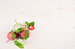 Freshly blended green and red fruit smoothie in glass jars with straw, mint leafs, top view. White wooden board background, copy space Stock Image