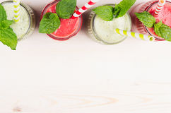 Freshly blended green and red fruit smoothie of strawberry and apple in glass jars with straw, mint leafs, top view. White wooden. Freshly blended green and red Royalty Free Stock Photo
