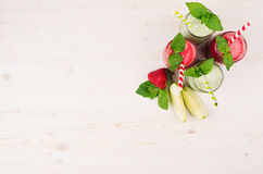 Freshly blended green and red fruit smoothie of strawberry and apple in glass jars with straw, mint leafs, top view. Stock Photos