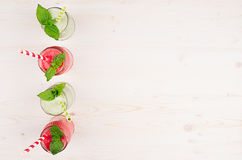 Freshly blended green and red fruit smoothie of strawberry and apple in glass jars with straw, mint leafs, top view. White wooden board background, copy space Stock Images