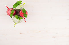Freshly blended green and red fruit smoothie of strawberry and apple in glass jars with straw, mint leafs, top view. White wooden board background, copy space Royalty Free Stock Photography