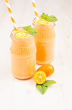 Freshly blended orange citrus kumquat fruit smoothie in glass jars with straw, mint leaf, cute ripe berry, close up. Stock Photography