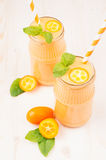 Freshly blended orange citrus kumquat fruit smoothie in glass jars with straw, mint leaf, cute ripe berry, close up. Royalty Free Stock Photo