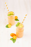 Freshly blended orange citrus kumquat  fruit smoothie in glass jars with straw, mint leaf, cute ripe berry, copy space. White wooden board background, vertical Stock Photos