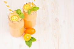 Freshly blended orange citrus kumquat fruit smoothie in glass jars with straw, mint leaf, cute ripe berry, copy space. Freshly blended orange citrus kumquat Stock Images