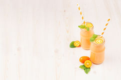 Freshly blended orange citrus kumquat  fruit smoothie in glass jars with straw, mint leaf, cute ripe berry, copy space. White wooden board background Royalty Free Stock Photo