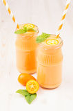 Freshly blended orange citrus kumquat fruit smoothie in glass jars with straw, mint leaf, cute ripe berry, copy space. Freshly blended orange citrus kumquat Royalty Free Stock Photo