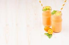 Freshly blended orange citrus kumquat fruit smoothie in glass jars with straw, mint leaf, cute ripe berry, copy space. Freshly blended orange citrus kumquat Stock Image