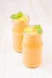 Freshly blended orange citrus kumquat fruit smoothie in glass jars with straw, mint leaf, cute ripe berry, copy space. Freshly blended orange citrus kumquat Royalty Free Stock Photos