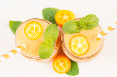 Freshly blended orange citrus kumquat  fruit smoothie in glass jars with straw, mint leaf, cute ripe berry, top view, close up. Royalty Free Stock Images