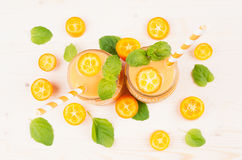 Freshly blended orange citrus kumquat fruit smoothie in glass jars with straw, mint leaf, cute ripe berry, top view, close up. Stock Image