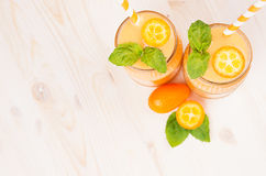 Freshly blended orange citrus kumquat  fruit smoothie in glass jars with straw, mint leaf, cute ripe berry, top view. White wooden board background, copy space Stock Image