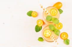Freshly blended orange citrus kumquat fruit smoothie in glass jars with straw, mint leaf, cute ripe berry, top view. Freshly blended orange citrus kumquat Royalty Free Stock Photos