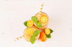 Freshly blended orange citrus kumquat fruit smoothie in glass jars with straw, mint leaf, cute ripe berry, top view. Freshly blended orange citrus kumquat Stock Images