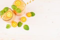 Freshly blended orange citrus kumquat fruit smoothie in glass jars with straw, mint leaf, cute ripe berry, top view. Freshly blended orange citrus kumquat Stock Photos