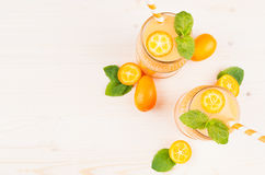 Freshly blended orange citrus kumquat  fruit smoothie in glass jars with straw, mint leaf, cute ripe berry, top view. White wooden board background, copy space Royalty Free Stock Images