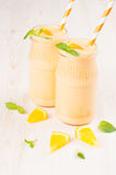 Freshly blended orange citrus smoothie in glass jars with straw, mint leaf, close up. White wooden board background Royalty Free Stock Photography