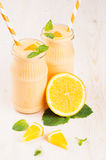 Freshly blended orange citrus smoothie in glass jars with straw, mint leaf, cut orange,  close up. White wooden board background Stock Photography