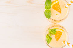 Freshly blended orange citrus smoothie in glass jars with straw, mint leaf, top view, close up. White wooden board background, copy space Royalty Free Stock Images