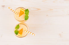 Freshly blended orange citrus smoothie in glass jars with straw, mint leaf, top view, close up. White wooden board background, copy space Stock Image