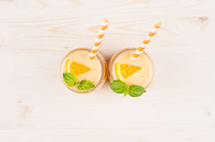 Freshly blended orange citrus smoothie in glass jars with straw, mint leaf, top view, close up. White wooden board background, copy space Stock Photo