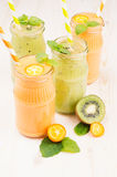 Freshly blended orange kumquat and green kiwi fruit smoothie in glass jars with straw, mint leaf, cut ripe berry, close up. Stock Photography