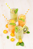 Freshly blended orange kumquat and green kiwi fruit smoothie in glass jars with straw, mint leaf, cut ripe berry, close up. White wooden board background Royalty Free Stock Photos