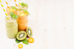 Freshly blended orange kumquat and green kiwi fruit smoothie in glass jars with straw, mint leaf, cut ripe berry, copy space. Stock Photos