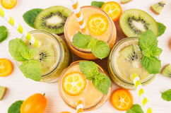 Freshly blended orange kumquat and green kiwi fruit smoothie in glass jars with straw, mint leaf, cut ripe berry, top view, close Stock Photo