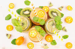 Freshly blended orange kumquat and green kiwi fruit smoothie in glass jars with straw, mint leaf, cut ripe berry, top view, close. Up. White wooden board Royalty Free Stock Photo