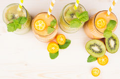 Freshly blended orange kumquat and green kiwi fruit smoothie in glass jars with straw, mint leaf, cut ripe berry, top view. White wooden board background, copy Stock Photos